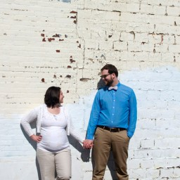 Pregnant couple in front of wall