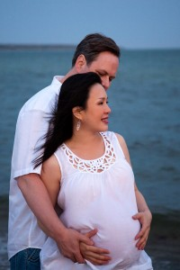 Pregnant couple in front of ocean