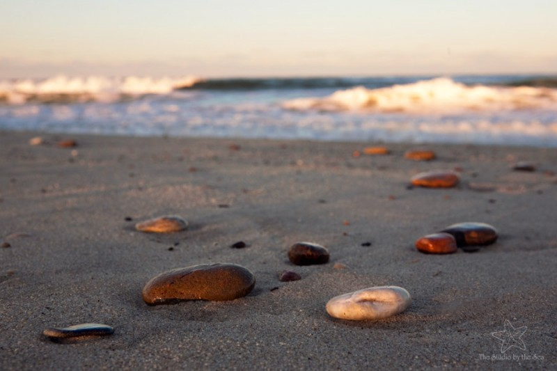 rocks on sand with ocean