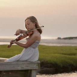 Young girl playing violin by the ocean