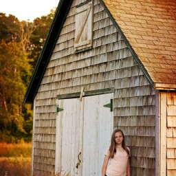 girl in field by barn