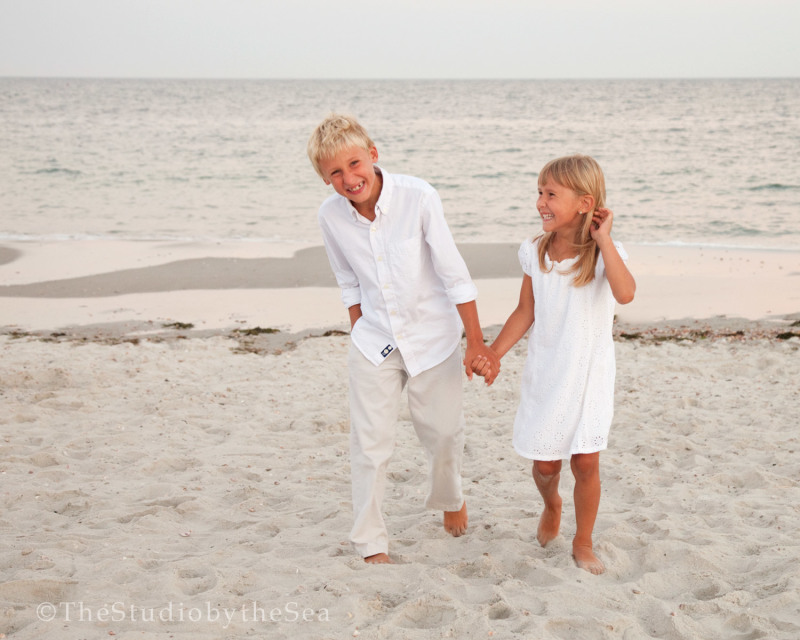 two kids laughing walking on the beach