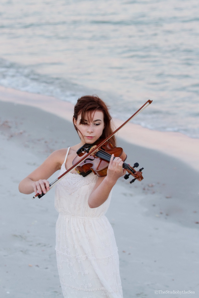 Senior girl playing violin by the sea